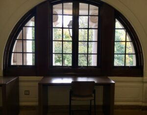 Study desk set under arched windows on the second floor.
