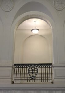 """Ornate railings with the letter """"P"""" encase the hallways connecting to the stairway."""
